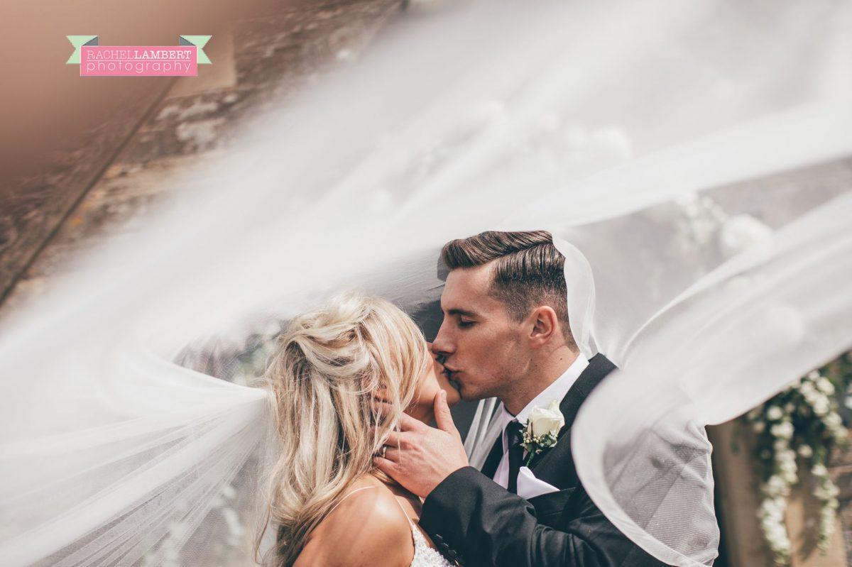 bride and groom portrait outside church wedding long veil