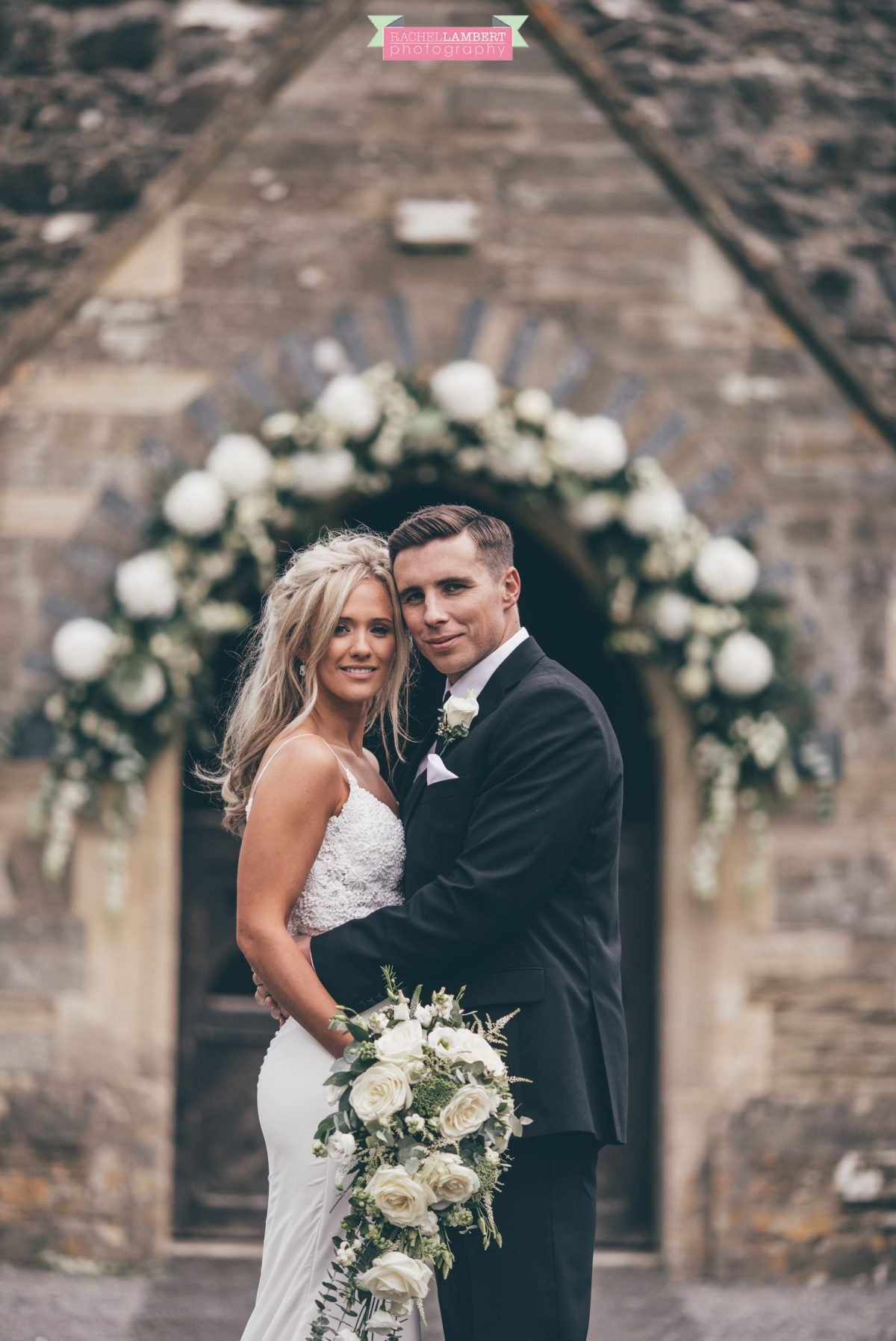 bride and groom outside church wedding flower arch bridal flowers