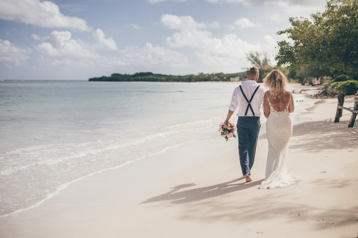 beach destination wedding photographer in jamaica bride and groom walking rachel lambert photography