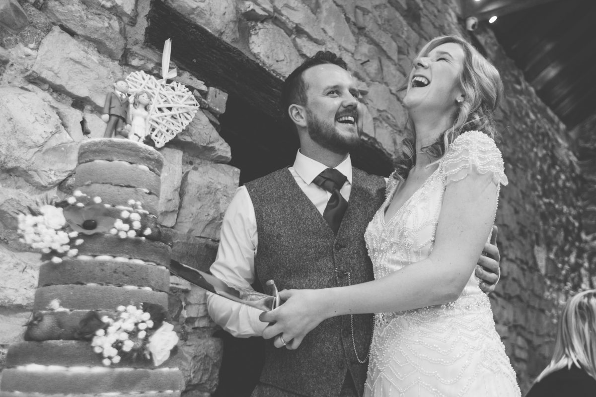 cake cutting shot of the bride and groom laughing pencoed house wedding rachel lambert photography
