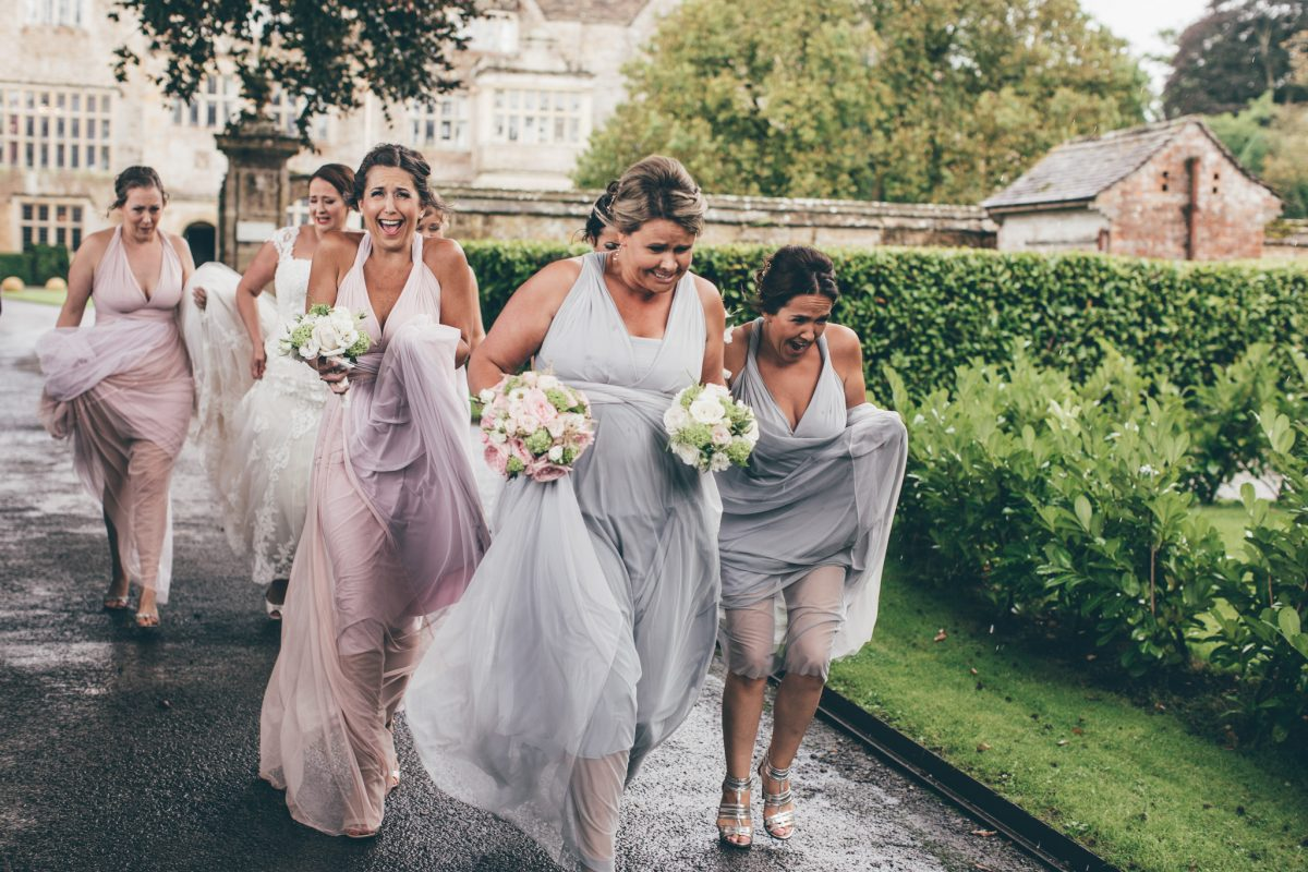 bridesmaids running to the church in the rain rachel lambert photography north cadbury court