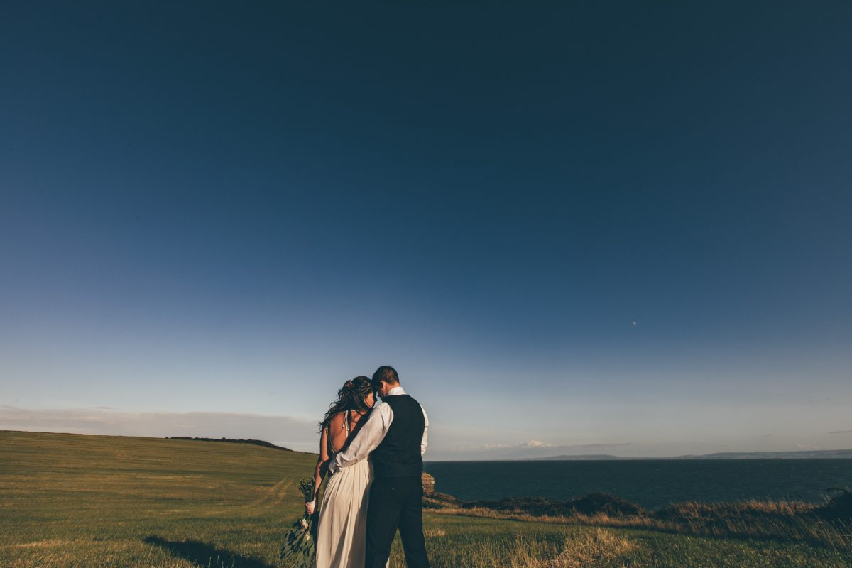 bride and groom cliff top at rosedew farm summer wedding rachel lambert photography