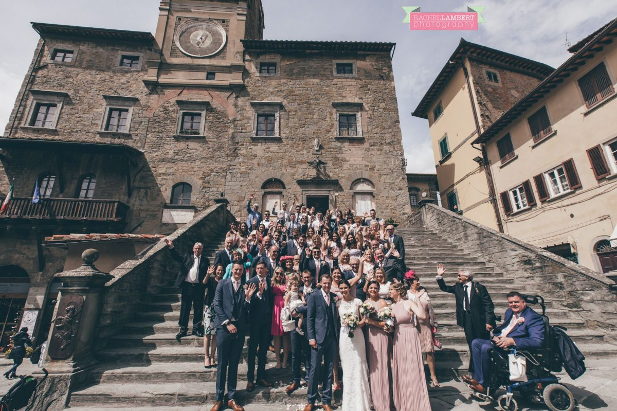 bride and groom portrait wedding in italy colour cortona tuscany group shot on steps at town hall